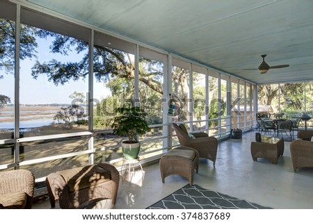 Outdoor screen porch with waterfront view and furniture - stock photo