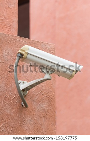 outdoor security camera on orange wall - stock photo