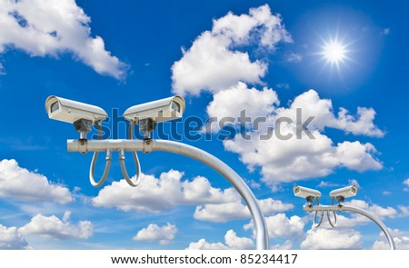 outdoor security cctv cameras against blue sky and sunshine - stock photo