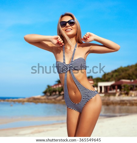 Outdoor sensual closeup of pretty young blonde smiling happy woman posing on vacation in bikini on the beach
