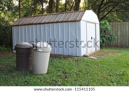 Outdoor shed with covered trash cans - stock photo