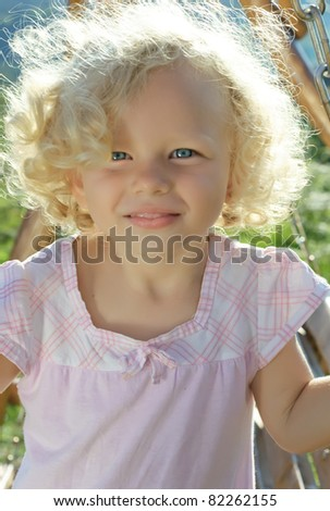Outdoor shoot of little funny blonde curly girl