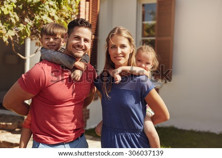 Outdoor shot of a happy couple carrying their children on their backs. Portrait of a mother and father giving their children piggyback rides in the backyard. - stock photo