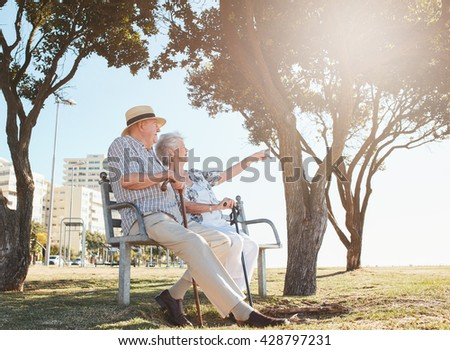 Outdoor shot of a senior couple sitting on a park bench with woman showing something interesting to her  husband. Retired couple taking a break and relaxing on a bench. - stock photo