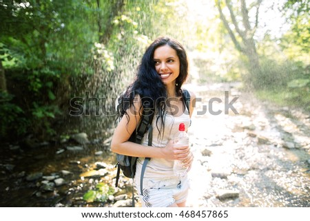Outdoor shot of attractive young woman with backpack standing in a mountain stream. Female hiker in creek water.Portrait of young woman holding bottle of water. Happy woman enjoying tropical rain