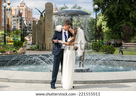 Outdoor shot of bride and groom dancing near fountain at park - stock photo