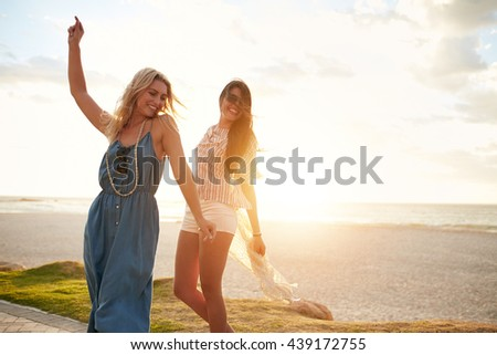Outdoor shot of cheerful young women enjoying and dancing on a beach. Female friends having fun on the sea shore on a sunny day. - stock photo