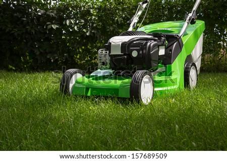 Outdoor shot of green lawnmower - stock photo