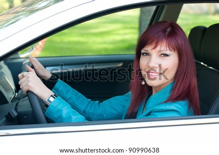 Outdoor shot of happy female red-haired driver sitting in her new car - stock photo