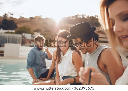 Outdoor shot of happy young man sitting by the pool with his friends partying. Group of young people hanging around a swimming pool having party. Men and women enjoying rooftop party. - stock photo