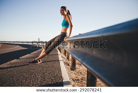 Outdoor shot of happy young woman sitting on highway guardrail after a morning run. Fit woman on country road taking a break after outdoor workout. - stock photo