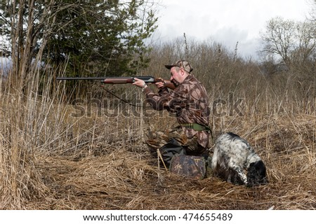 Outdoor shot of man with a gun and Russian hunting Spaniel.