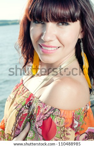 Outdoor shot of smiling young woman standing near the shore - stock photo