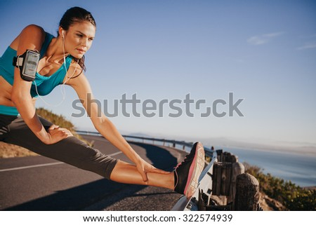 Outdoor shot of woman stretching her legs before a run. Determined runner preparing for outdoor training looking away. - stock photo