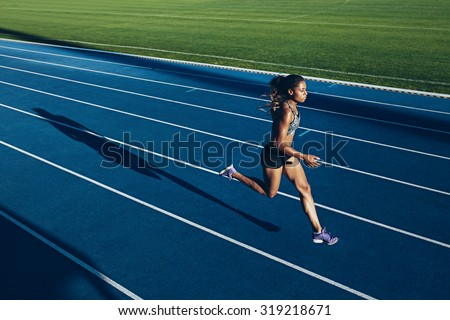 Outdoor shot of young African woman athlete running on racetrack. Professional sportswoman during running training session. - stock photo
