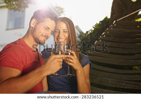 Outdoor shot of young caucasian couple in backyard toasting wine smiling. Romantic couple relaxing on hammock celebrating with wine. - stock photo