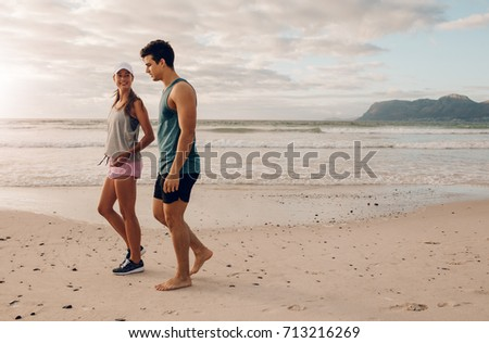 Outdoor shot of young couple on walking along the shore. Young man and woman strolling on beach in morning.