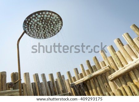 Outdoor shower with water coming out of the head and blue sky behind - stock photo