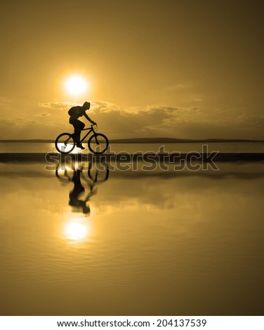 Outdoor silhouette of fit cyclist in cap at sunset with a blurred reflection in water with ripples ride along seashore summer beach at  evening horizon sea yellow sunset cloudy sky background  - stock photo