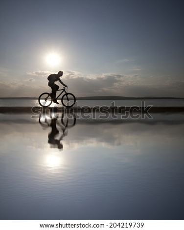 Outdoor silhouette of fit cyclist in cap at sunset with a blurred reflection in water with ripples ride along seashore summer beach at blue evening horizon sea yellow sunset cloudy sky background