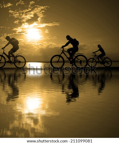 Outdoor silhouette of three fit group or team cyclist in at sunset with reflection in water with ripples ride along seashore summer beach at yellow evening horizon sea sunset cloudy sky background - stock photo
