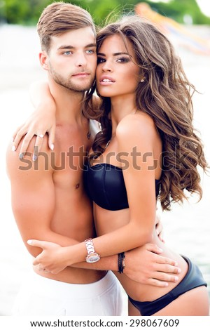 Outdoor Skinny sporty tanned teen couple in striped bikini posing,lying on sandy beach and sunbathing together,beautiful couple,lovely teenagers,honeymoon,married,romantic holidays,lovely couple beach - stock photo