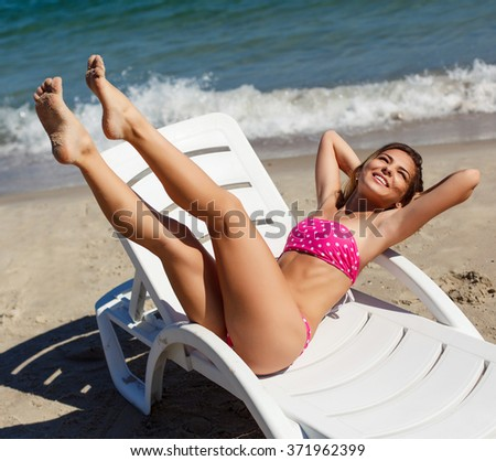 Outdoor smiling happy portrait of beautiful blonde woman tanned fashion having fun and lying on the beach with sexy long legs
