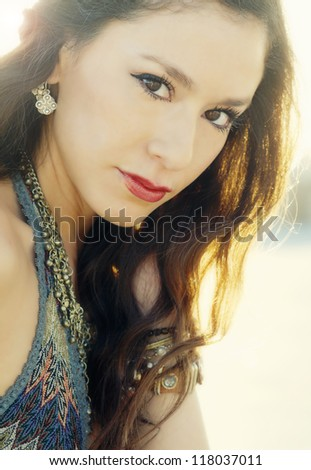 Outdoor soft sunny portrait of beautiful young woman in boho style