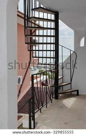 Outdoor Spiral Staircase Leading To The Loft And Mediterranean  Seascape In The Background - stock photo
