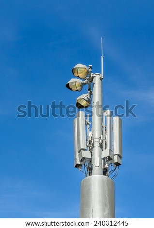 Outdoor stadium lights and telecommunication tower against daytime blue sky.Single row of bulbs,cell phone gsm antennas on tall metal pole.Room for text, copyspace.Blue sky,wispy clouds.Vertical view  - stock photo