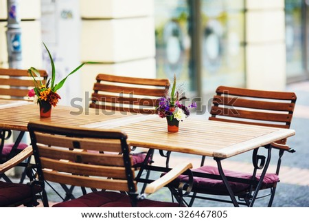 Outdoor street cafe tables ready for service. Shallow DOF. Street cafe decorated with a bouquet of flowers. Wooden table and chairs. - stock photo