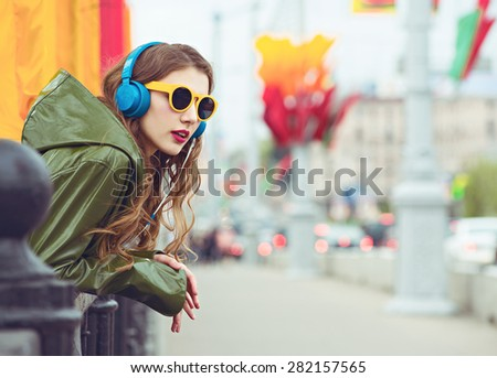 outdoor street style hipster dj woman in yellow sunglasses and dj headphones listen music and smile - stock photo