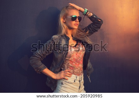 Outdoor summer closeup portrait of young stylish fashion glamorous woman or girl in sunny day on street jeans jacket and sunglasses standing near blue wall - stock photo