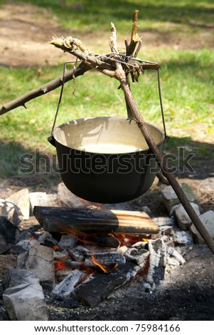 Outdoor summer. Cooks porridge in a pot on the fire - stock photo