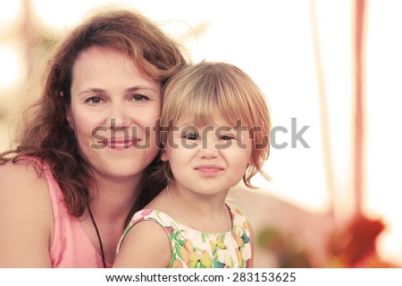 Outdoor summer evening portrait of a real Caucasian family, young mother with her small cute daughter, warm toned photo, old style instagram filter effect - stock photo