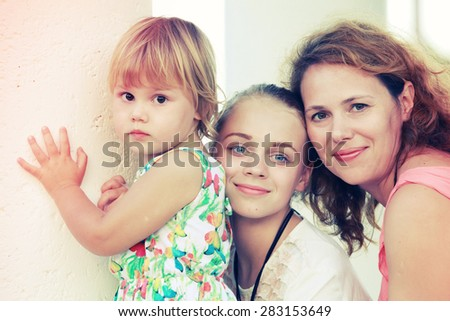 Outdoor summer evening portrait of a real Caucasian family, young mother with her two daughters, colorful toned photo, old style instagram style filter effect - stock photo