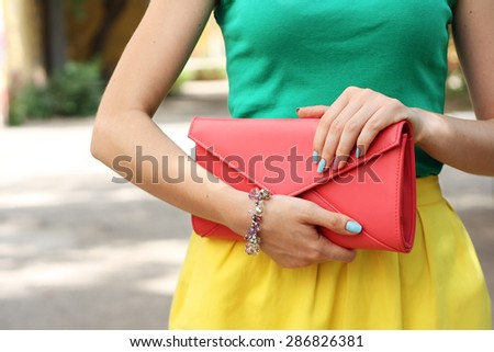 Outdoor summer fashion girl with coral orange handbag clutch . Summer outfit - stock photo