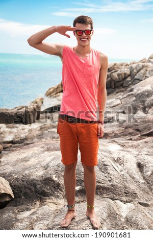 Outdoor summer fashion portrait of happy smiling young man having fun at stone beach. Enjoying summer time. - stock photo