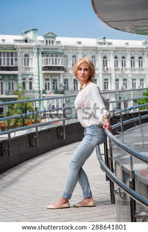 Outdoor summer fashion stunning portrait on pretty young blonde sexy woman dressed in a white shirt and torn jeans having fun in the street. - stock photo