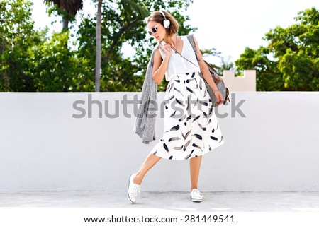 Outdoor summer lifestyle fashion portrait of young hipster stylish woman walking on the street, wearing vintage clothes and earphones, clear fresh colors. - stock photo