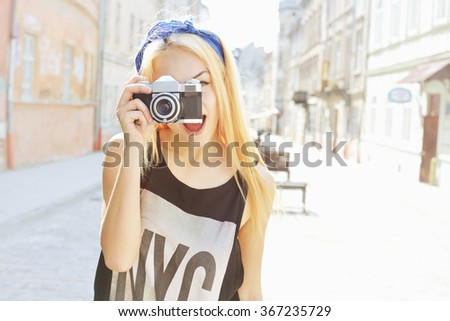 Outdoor summer lifestyle portrait of pretty woman having fun in city with camera. Travel photo of photographer. Making pictures, hipster style. Blonde girl looking at camera. Young woman taking photo - stock photo