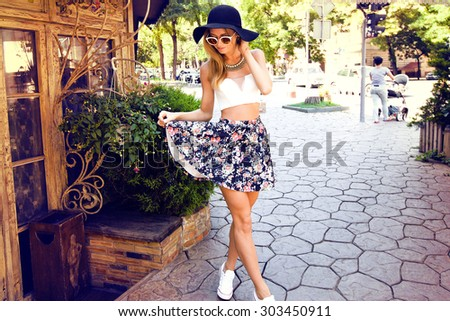 Outdoor Summer lifestyle portrait of woman wearing hipster outfit and sunglasses, smiling,having fun in cafe, sunny colors, trendy clothes.mini skirt,street fashion style,hat,retro,street cafe,meeting - stock photo