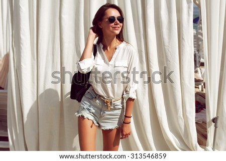 Outdoor summer portrait of pretty beautiful young stylish fashion sensual brunette girl having fun in jeans shorts and sunglasses