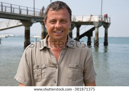 Outdoor summer portrait of smiling happy man in casual on the beach