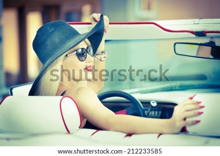 Outdoor summer portrait of stylish blonde vintage woman driving a convertible red retro car. Fashionable attractive fair hair female with black hat in red vehicle. Sunny bright colors, outdoors shot. - stock photo