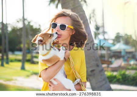 Outdoor summer portrait of stylish swag girl with dog at the park,smiling and having fun during their vacation,wear summer sunglasses,summer bright clothes,yellow summer shirt and white skirt. - stock photo