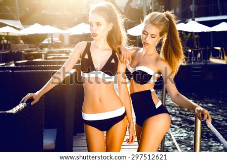 Outdoor summer portrait of two young pretty girls,looking to the ocean at tropical beach, enjoy freedom and fresh air,wearing stylish bikini and clothes.Posing opposite sunset,toned,elegant swimsuits - stock photo