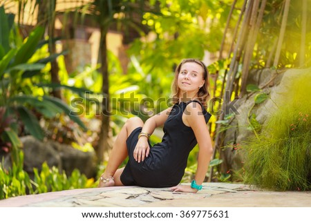Outdoor summer portrait of young beautiful girl with blond hair posing in short black stylish dress in tropical park - stock photo