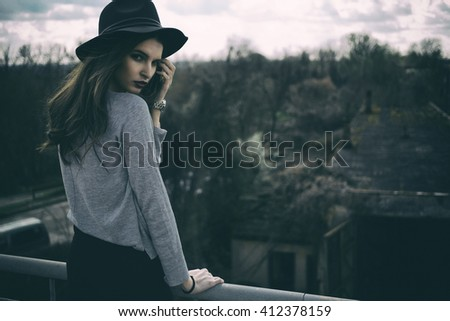 Outdoor summer portrait of young pretty cute girl. Beautiful woman posing at sunset. Woman in white hat and scarf standing near old pier rails. Photo has an INTERNATIONAL FILM GRAIN.  - stock photo