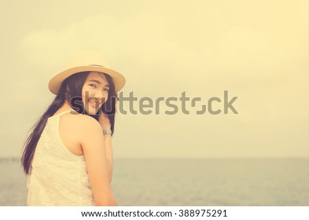 Outdoor summer portrait of young pretty woman looking to the ocean at tropical beach, enjoy her freedom and fresh air, wearing stylish hat and clothes, Vintage filtered image. - stock photo